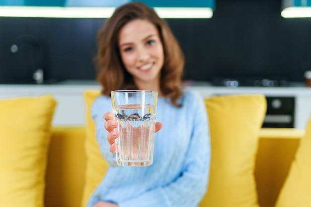 Hermosa joven feliz con un vaso de agua cristalina sentado en el sofá amarillo suave. Foto Premium