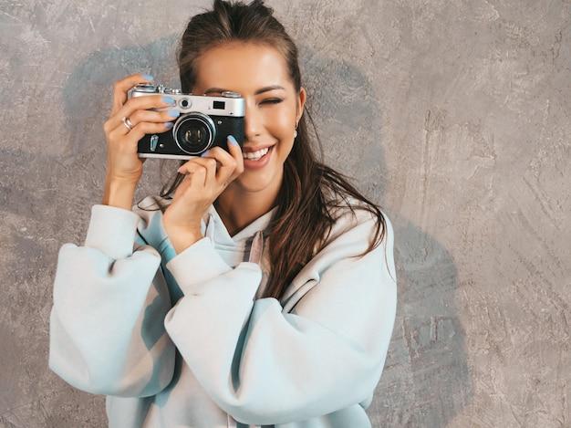 Hermosa joven fotógrafo sonriente chica tomando fotos con su cámara retro. mujer haciendo fotos. Foto gratis