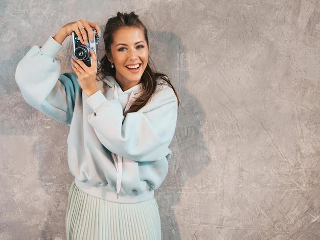 Hermosa joven fotógrafo sonriente chica tomando fotos con su cámara retro. Foto gratis