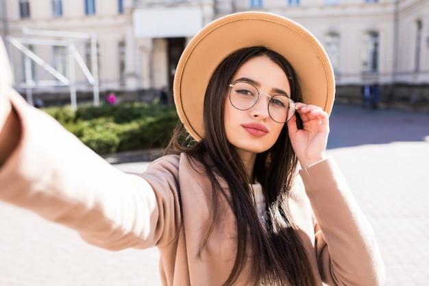 Hermosa joven hace selfie en su nuevo teléfono inteligente al aire libre en la ciudad en un día soleado Foto gratis