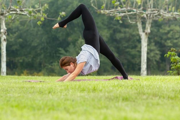 Hermosa joven haciendo ejercicios de yoga en el parque verde Foto gratis