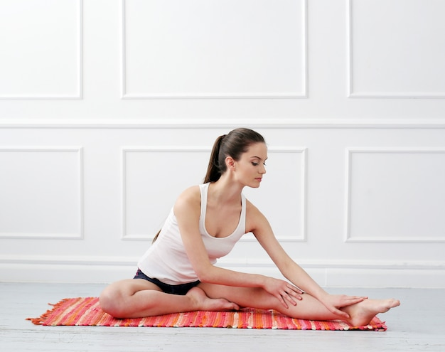 Hermosa joven haciendo yoga Foto gratis