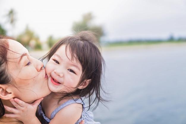 Hermosa joven madre con hija en el fondo de la playa Foto Premium