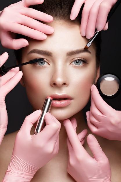 Hermosa joven con maquillaje natural nude con herramientas cosméticas en manos, rostro de belleza, Foto Premium
