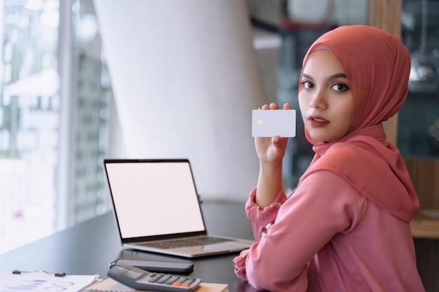 Hermosa joven mujer de negocios musulmana asiática en hijab rosa y ropa casual con portátil de pantalla blanca y manos mostrando una tarjeta de crédito vacía blanca Foto Premium