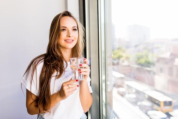 Hermosa joven o mujer con un vaso de agua cerca de la ventana con camisa blanca y bata gris Foto gratis