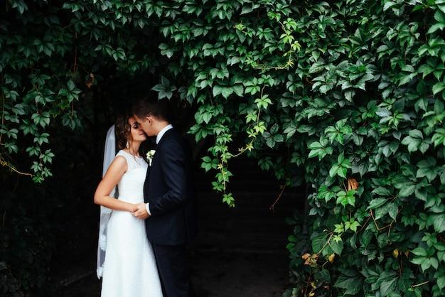 Hermosa joven pareja besándose, novia rubia con flor Foto Premium