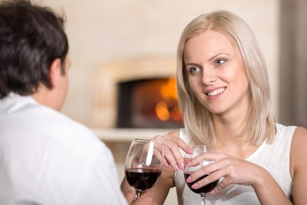 Hermosa joven pareja está hablando y beber vino. Foto Premium