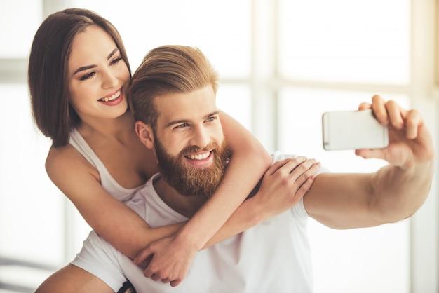 Hermosa joven pareja está haciendo selfie usando un teléfono inteligente. Foto Premium