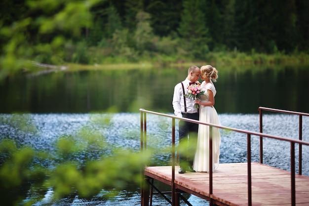 Hermosa joven pareja, novia y el novio posando en el fondo del lago. el novio y la novia en el muelle. Foto Premium