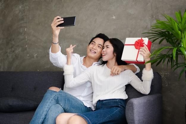 Hermosa joven pareja sostiene una caja de regalo, hace autofoto y sonríe mientras celebra en casa Foto Premium