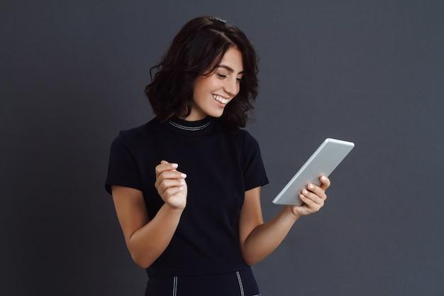 Hermosa joven posando sobre pared gris y sosteniendo la tableta en manos Foto gratis