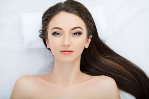 Hermosa joven recibiendo un tratamiento facial en el salón de belleza Foto Premium