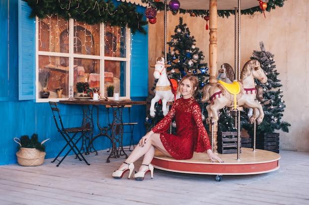 Hermosa joven se regocija cerca de un carrusel con caballos. navidad. Foto Premium