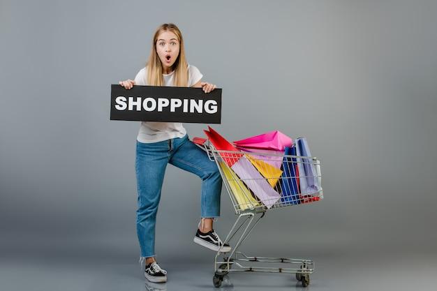 Hermosa joven rubia con signo de compras y carretilla de mano con coloridas bolsas aisladas sobre gris Foto Premium
