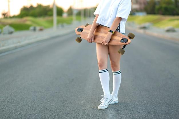 Hermosa joven sexy en shorts muy cortos caminando con longboard en tiempo soleado. ocio. estilo de vida saludable. deportes extremos. look de moda, retrato hipster al aire libre, bali, zapatillas de deporte, hipster, sunse Foto Premium