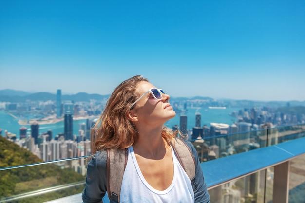 Hermosa joven sonríe alegremente y pone su rostro al sol Foto Premium