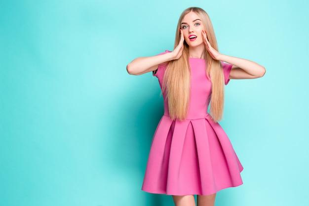Hermosa joven sonriente en mini vestido rosa posando en el estudio Foto gratis