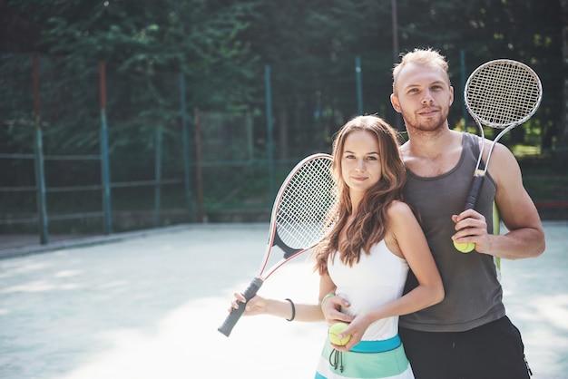 Una hermosa joven con su esposo pone en una cancha de tenis al aire libre. Foto gratis