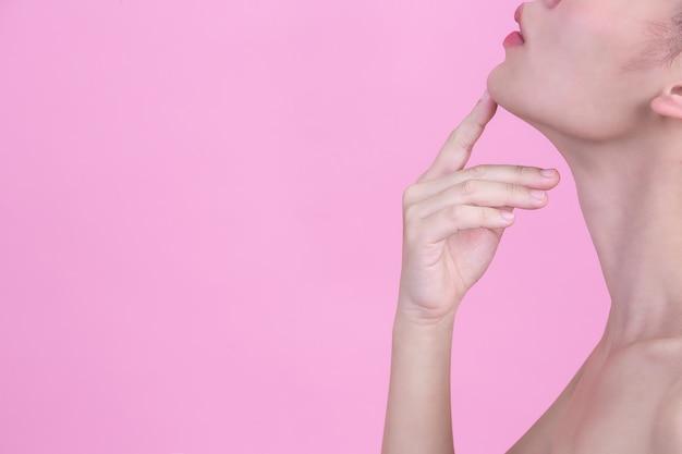 Hermosa joven toca su barbilla con su dedo índice en la pared de color rosa. Foto gratis