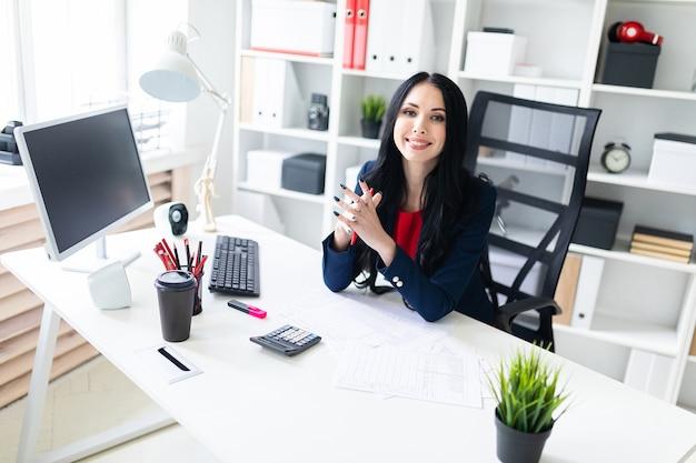 Hermosa joven trabajando con calculadora y documentos en la oficina en la mesa Foto Premium