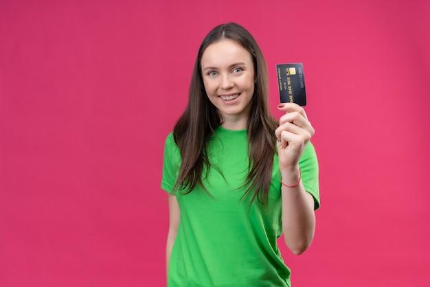 Hermosa joven vestida con camiseta verde con tarjeta de crédito sonriendo alegremente feliz y positivo de pie sobre fondo rosa aislado Foto gratis