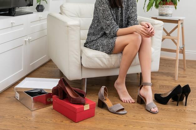 Una hermosa joven con un vestido corto se sienta en una silla en la sala de estar cerca del armario y elige un par de zapatos para usar hoy. una niña se prueba zapatos de tacón alto. concepto de compras web en línea Foto Premium