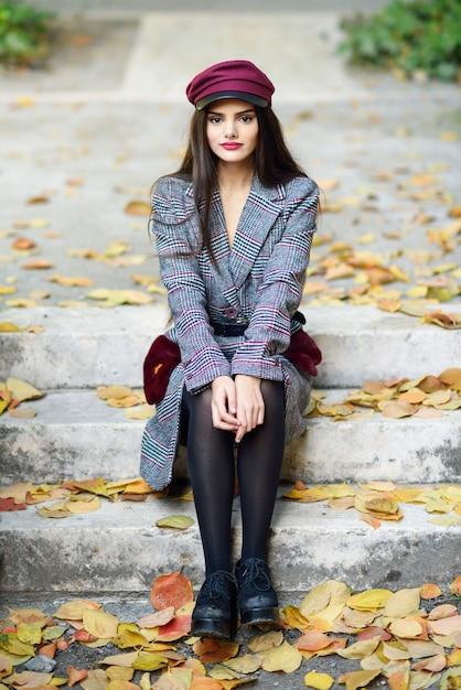 Hermosa joven vistiendo abrigo y gorra de invierno sentado en pasos llenos de hojas de otoño Foto Premium