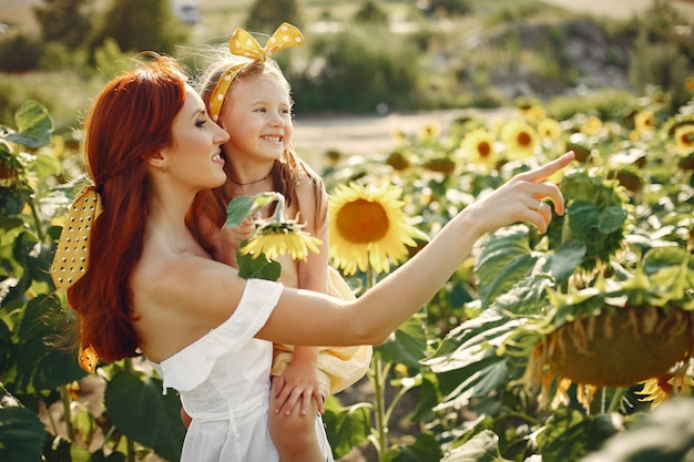Hermosa y linda familia en un campo con girasoles Foto gratis