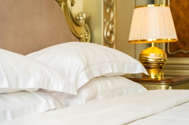 Hermosa y lujosa almohada blanca cómoda en la decoración de la cama en el dormitorio Foto gratis