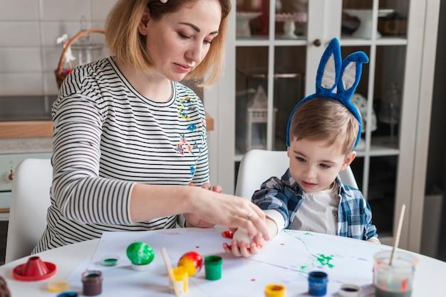 Hermosa madre enseñando a niño a pintar huevos Foto gratis