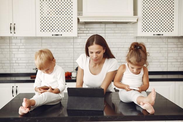 Hermosa madre con lindos hijos en casa en una cocina Foto gratis