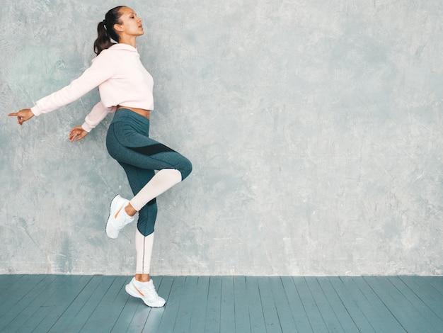 Hermosa modelo con cuerpo bronceado perfecto. salto femenino en estudio cerca de la pared gris Foto gratis