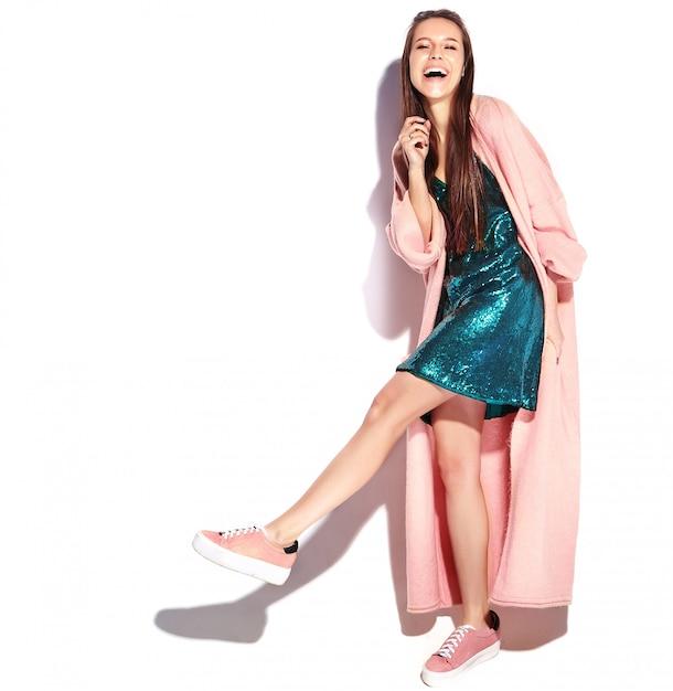 Hermosa modelo de mujer morena hipster sonriente en elegante abrigo rosa. caminar, de cuerpo entero Foto gratis
