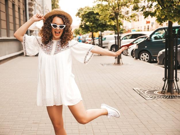 Hermosa modelo sonriente con peinado afro rizos vestido con vestido blanco hipster de verano. Foto gratis