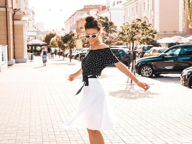 Hermosa modelo sonriente vestida con ropa elegante de verano. chica despreocupada sexy bailando en la calle. empresaria moderna moderna en gafas de sol divirtiéndose en movimiento Foto gratis