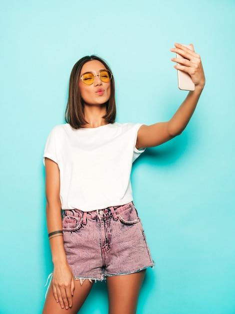 Hermosa modelo sonriente vestida con ropa hipster de verano. chica despreocupada sexy posando en estudio junto a la pared azul en shorts de jeans. mujer de moda y divertida tomando fotos de autorretrato selfie en teléfono inteligente Foto gratis