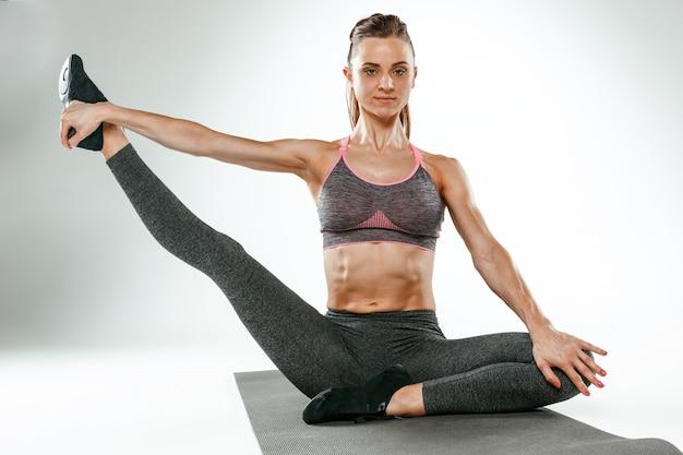 Hermosa morena delgada haciendo algunos ejercicios de estiramiento en un gimnasio Foto gratis