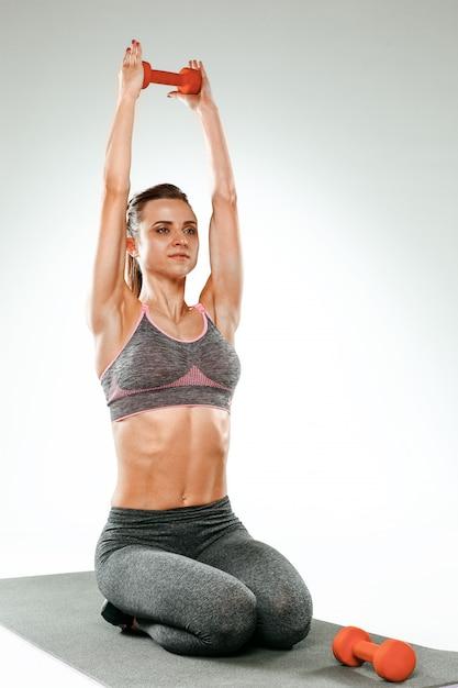 Hermosa morena delgada haciendo algunos ejercicios de estiramiento Foto gratis