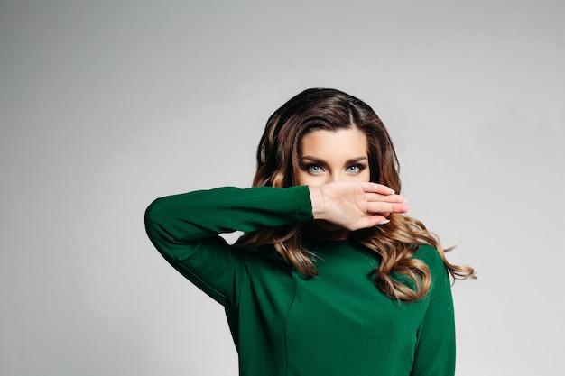 Hermosa morena con un vestido verde con ojos azules y cabello rizado, mira a la cámara y se cubre suavemente la boca con la mano derecha. aislar sobre un fondo gris Foto Premium