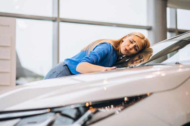 Hermosa mujer abrazando un automóvil en un showrrom de automóviles Foto gratis