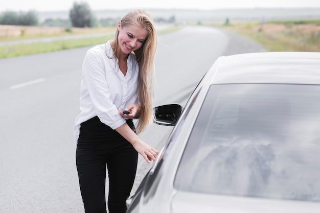 Hermosa mujer abriendo la puerta del auto Foto gratis