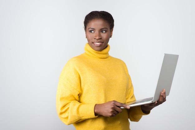 Hermosa mujer afroamericana sonriente con laptop Foto gratis