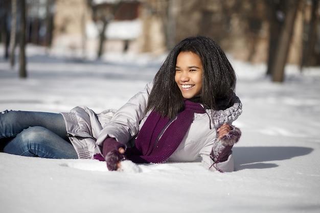 Hermosa mujer americana negra sonriente tumbado en la nieve al aire libre Foto gratis