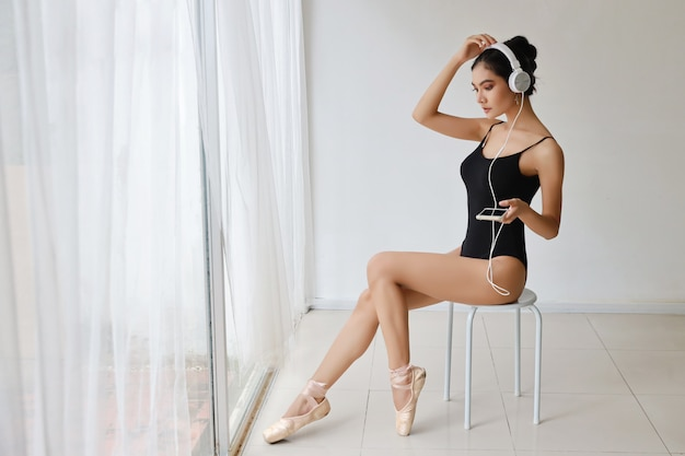 Hermosa mujer asiática joven sana y deportiva en ropa deportiva negra sentada con auriculares, escuchando música desde el teléfono móvil mientras entrena ballet bailando en la pared blanca. tecnología y concepto saludable Foto Premium