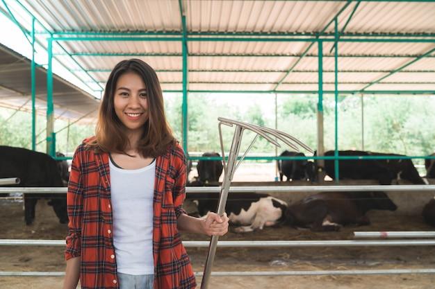 Hermosa mujer asiática o granjero con y vacas en el establo en la granja de productos lácteos-agricultura Foto gratis