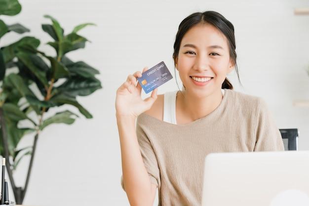 Hermosa mujer asiática usando una computadora o laptop comprando compras en línea Foto gratis
