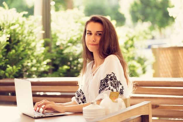 Hermosa mujer atractiva en el café con una computadora portátil con un coffee break Foto Premium