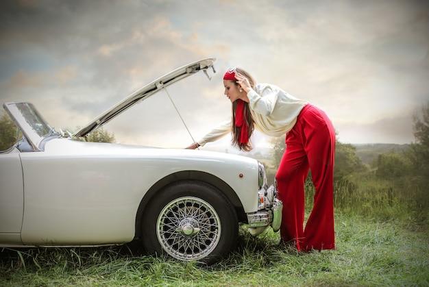 Hermosa mujer en una aventura con un auto deportivo Foto Premium