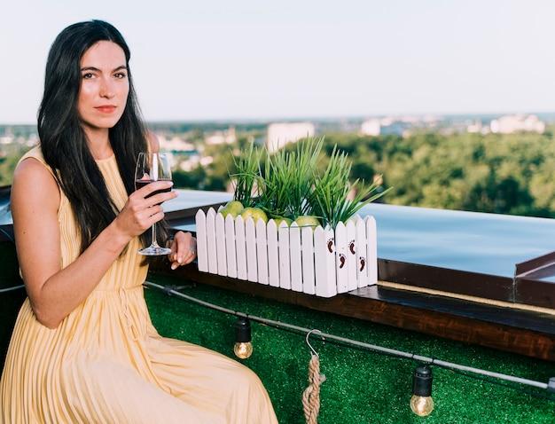Hermosa mujer bebiendo vino en la azotea Foto gratis